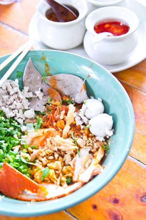 Serving of dry rice noodle with pork and vegetable on wooden table