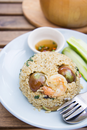Spicy green curry fired rice with shrimps on wooden table Stock Photo
