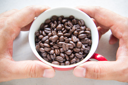 Man hand holding a red cup of roasted coffee Stock Photo