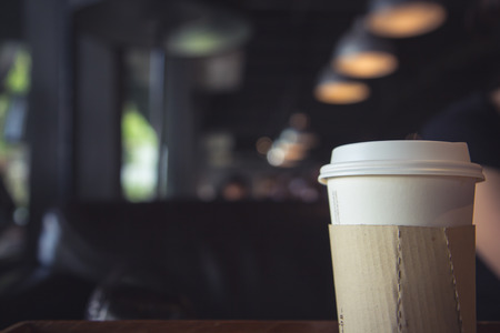 closeup of a hot paper cup of coffee at coffee shop