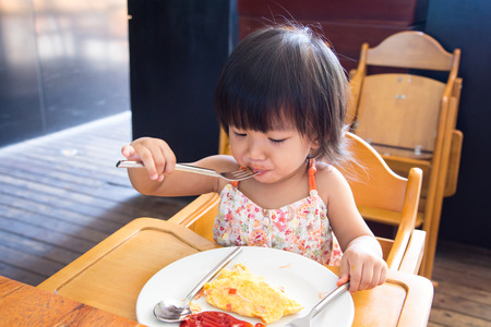 A Little asian girl eating omlet and siting on wooden chair in the restaurant