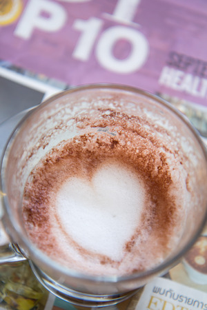 Finish a cup of cappucino with heart shape on bubble milk