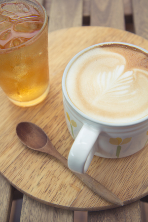 Cup of latte coffee with cold tea on wooden tray Stock Photo