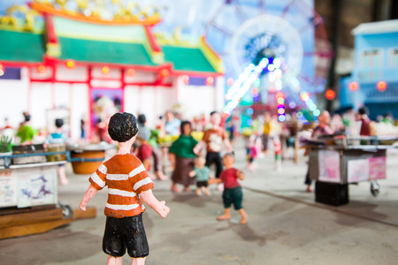 Lighting on the ferris wheel and temple at night with traditional craft dolls Stock Photo