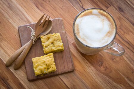 Latte art coffee on wooden cup with pumpkin blondies