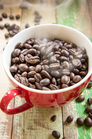 roasted coffee beans in red cup with coffee background Stock Photo