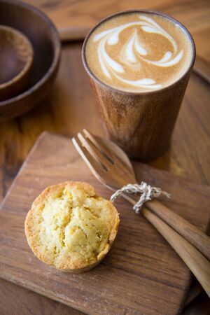 Latte art coffee on wooden cup with pumpkin muffin Stock Photo