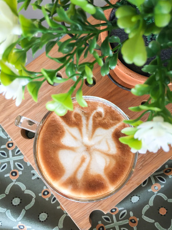 capacino: Butterfly shape of latte art coffee on wooden background