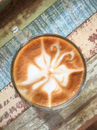 Butterfly shape of latte art coffee on wooden background