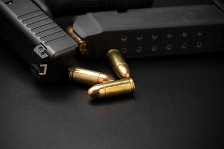 Close up of 9 mm.bullets with magazine and automatic handgun on black background (Selective focus)