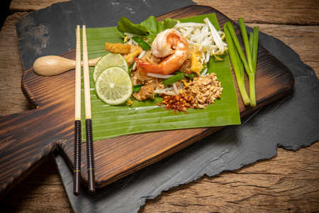 Thai style noodle or Pad Thai on cutting board with wooden background , Traditional food , Pad Thai is another famous Thai food , That foreigners know all over the world