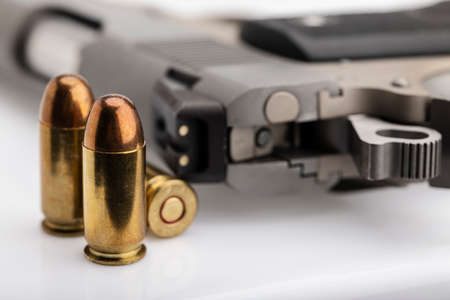 .45 or 11 mm. ammunitions and automatic hand gun on white background