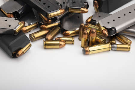 Pile of gun magazines and bullets on white background
