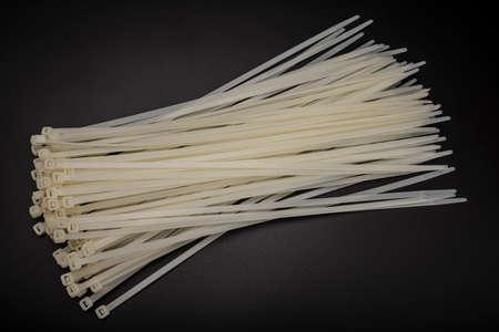 White nylon cable tie or zip tie on black background
