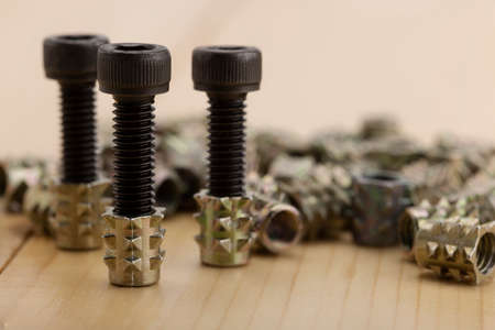Steel anchor bolts on wooden background , Equipment for wood construction