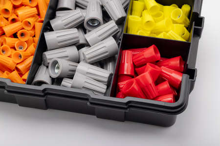 Many colored wire nuts in plastic box on white background , Tool for connecting electrical wires