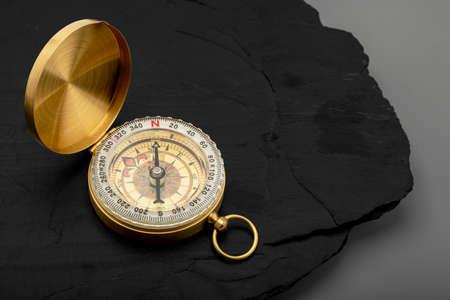 Classic compass, navigational compass on black stone background Фото со стока