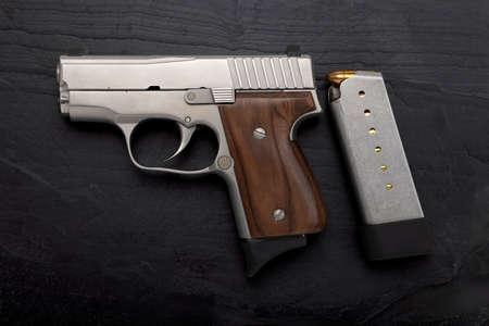 Semi-automatic handgun on black slate background Фото со стока