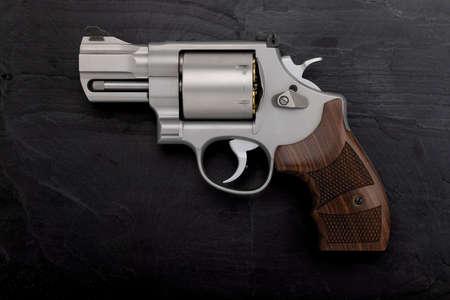.44 magnum revolver handgun on black slate background