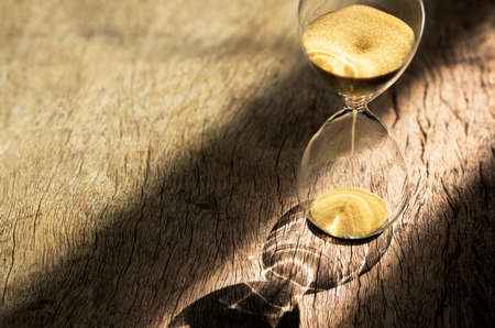 Sand clock , Hourglass as time passing on wooden background , Life time concept Фото со стока