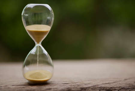 Sand clock , Hourglass as time passing on green nature background , Life time concept