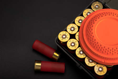 Clay shooting target with shotgun shell and box on black slate background , Shotgun game