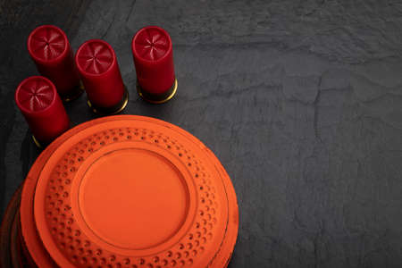 Clay shooting target with shotgun shell on black slate background , Shotgun game Фото со стока