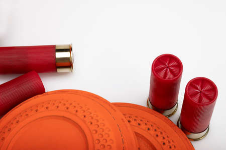Clay shooting target with shotgun shells on white isolated background , Shotgun game Фото со стока