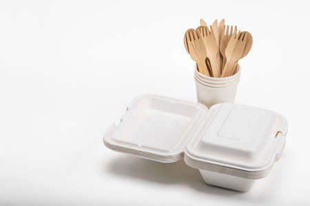 Wooden spoon and fork with knives and bagasse food box   , disposable tableware on white background. Eco-friendly materials Фото со стока