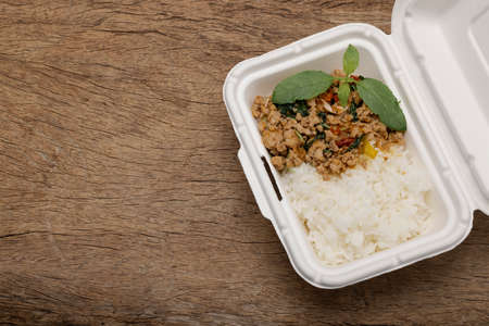 Spicy minced pork basil topping with rice in bagasse lunch box on wooden background