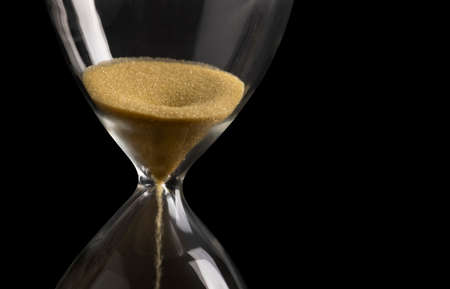 Sand clock , Hourglass as time passing on isolated black background , Life time concept