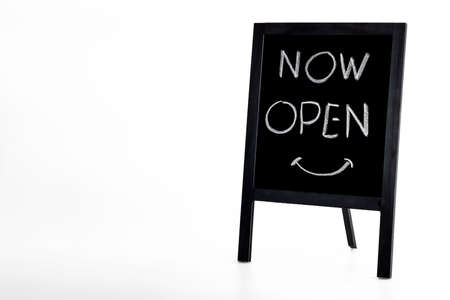 Hand writing 'Now Open' on small wooden vintage chalkboard on white background