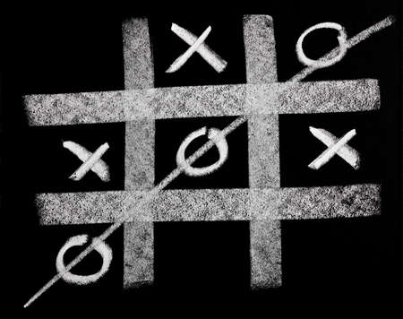 Tic Tac Toe , XO game competition challenge on black board background Фото со стока