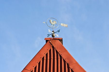 Vane on the roof of a country house on a background of blue sky