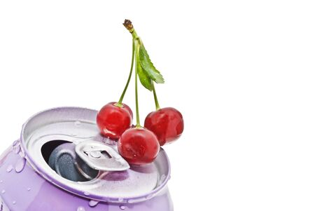 Three ripe red cherries lie on a tin photo
