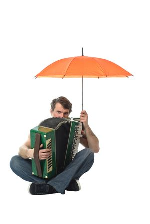 Accordion player- man sitting on the floor, in the hands holding an orange umbrella photo