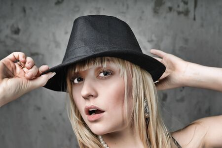 Blonde woman holding hands black hat photo