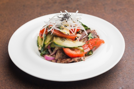 ensalada cesar: Placa con bocados en la mesa en el restaurante-trozos de carne, queso Foto de archivo