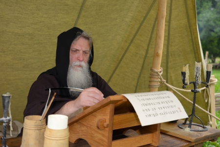Bearded monk chronicler writes on the historic festival ancient scroll photo