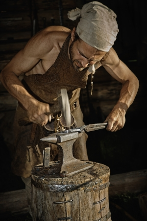 medieval blacksmith: Molten metal handles medieval blacksmith on the anvil