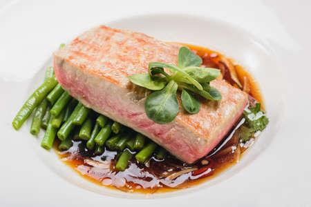 pesce cotto: pesce cotto in un piatto decorato con verdure