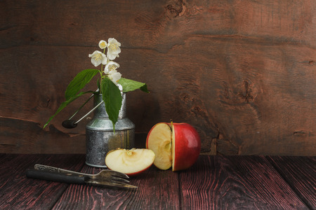 Still-life jasmine sprig of flowers in a metal can. Animates a photo of sliced apple and a cake fork with the knife