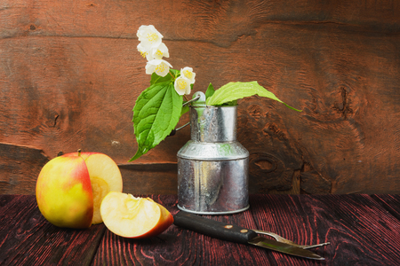 Still-life jasmine sprig of flowers in a metal bucket. Animates a photo of sliced apple and a cake fork with the knife