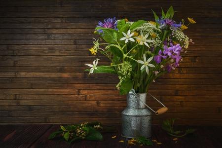 antique vase: Still life- wild flowers bouquet in vintage vase metal