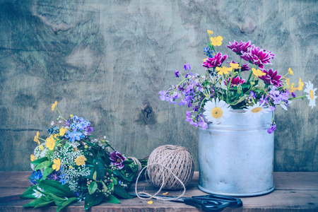 antique vase: Still life of wild flowers in an old metal bucket, twine, and scissors Stock Photo