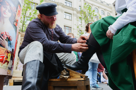MOSCOW, RUSSIA - June 1-12, 2017: International festival Times and epochs. The meeting. Reconstruction of historical eras - the street shoe shiner Editorial