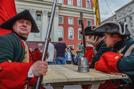 historical events: MOSCOW, RUSSIA - June 1-12, 2017: International festival Times and epochs. The meeting. Reenactors Infantry regiment of the time of Peter sitting at a wooden table