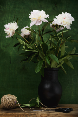 Still life- peony sprig of flowers in transparent glass jar