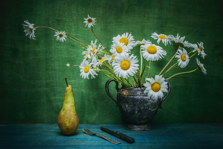 Still life painting- beautiful daisy flowers in a vase. Pear- wooden background. Banque d'images