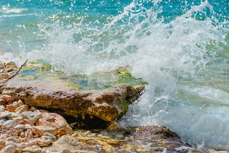 The sea and stones. Splashing waves- summer landscape. Seascape background.